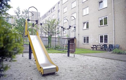 een gezamenlijke tuin met speeltoestellen voor de kinderen.