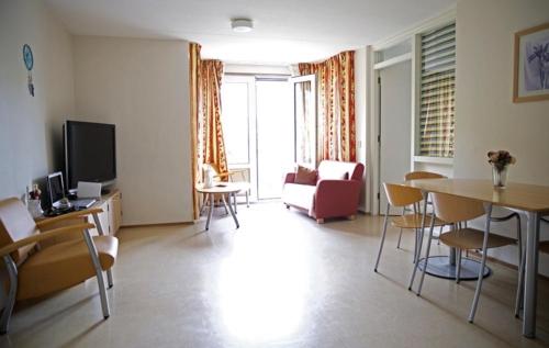 Een appartement met woonkamer, keuken, badkamer en één slaapkamer.